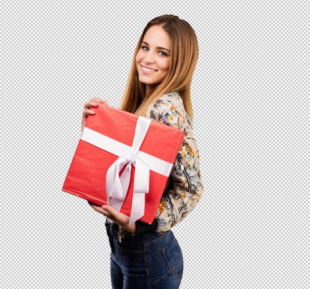 Giovane donna graziosa che tiene un regalo