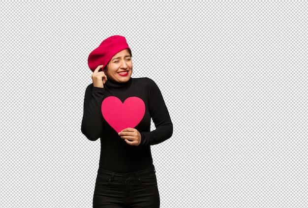 Giovane donna in giorno di san valentino che copre le orecchie con le mani