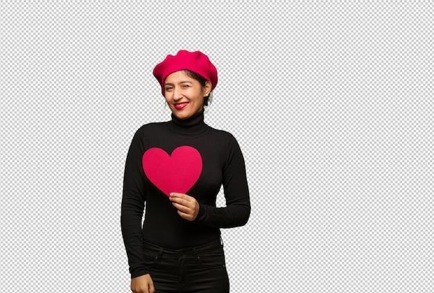 Giovane donna in san valentino ammiccante, gesto divertente, amichevole e spensierata