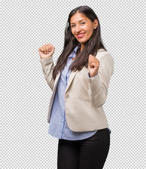 Giovane donna indiana che ascolta la musica, ballando e divertendosi, muovendosi, gridando ed esprimendo felicità, concetto di libertà
