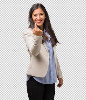 Giovane donna indiana di affari che invita a venire, sicuro e sorridente che fa un gesto con