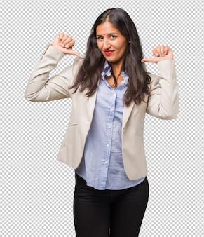 Giovane donna indiana orgogliosa e fiduciosa, indicando le dita, esempio da seguire, concetto di soddisfazione, arroganza e salute