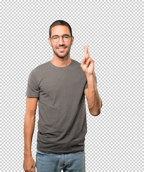 Giovane felice che fa un gesto incrociato delle dita