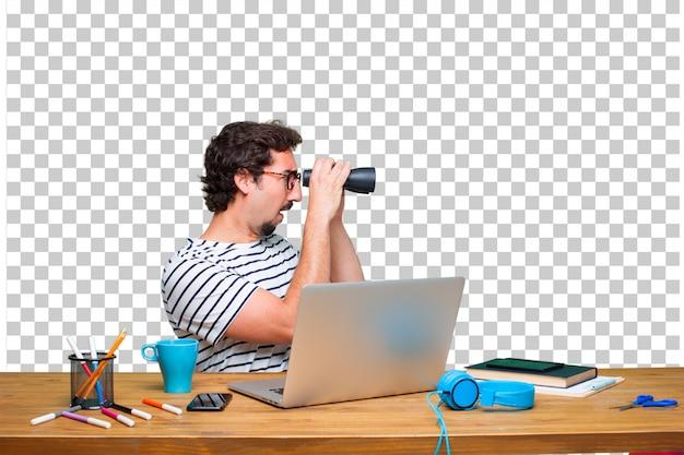 Giovane grafico pazzo su una scrivania con un computer portatile e con il binocolo