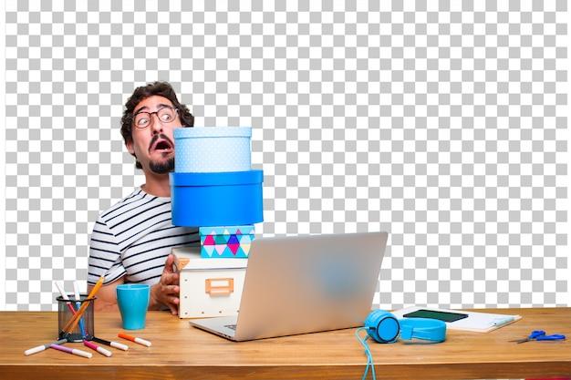 Giovane grafico pazzo su una scrivania con un computer portatile e con il concetto di scatola regalo