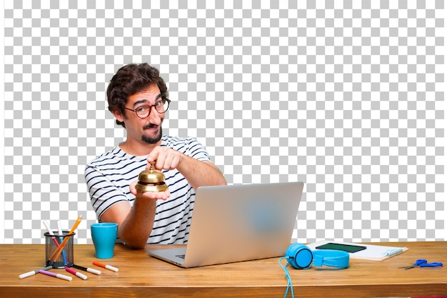 Giovane grafico pazzo su una scrivania con un computer portatile e con un campanello