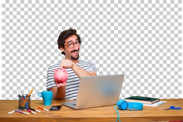 Giovane grafico pazzo su una scrivania con un computer portatile e con un salvadanaio