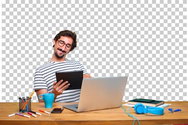 Giovane grafico pazzo su una scrivania con un computer portatile e con un tablet touch screen