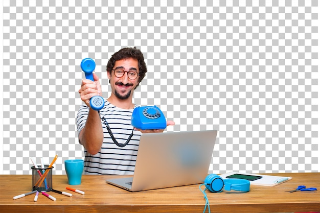 Giovane grafico pazzo su una scrivania con un computer portatile e con un telefono vintage