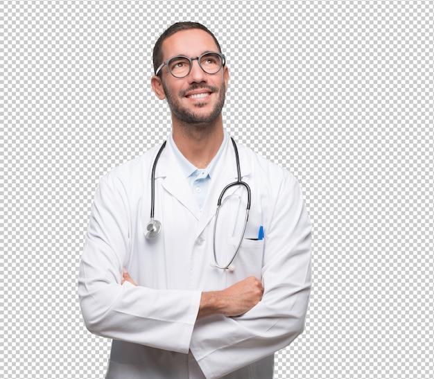 Giovane medico felice che osserva in su e che si domanda