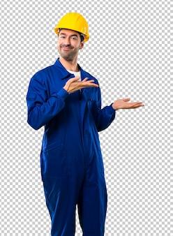 Giovane operaio con casco che estende le mani sul lato