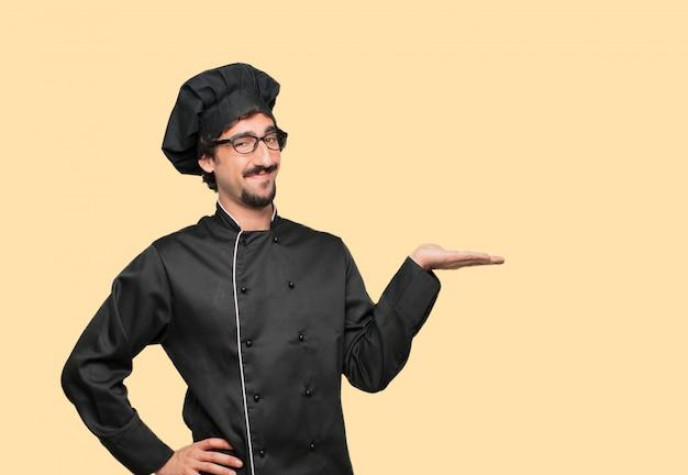 Giovane pazzo come uno chef sorridente con un'espressione soddisfatta che mostra un oggetto o un concetto