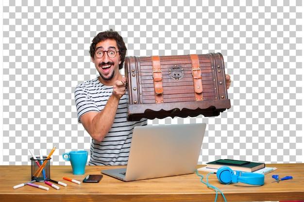 Giovane pazzo graphic designer su una scrivania con un computer portatile e con una cassa del pirata