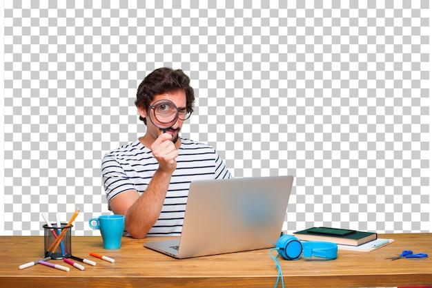 Giovane pazzo graphic designer su una scrivania con un computer portatile e con una lente di ingrandimento