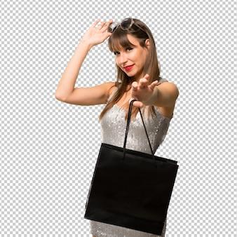 Giovane ragazza con gli occhiali da sole e con borse della spesa