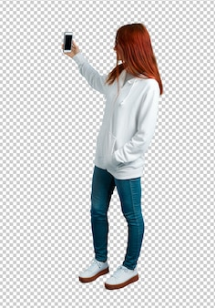 Giovane ragazza rossa in una felpa bianca urbana con gli occhiali prendendo un selfie con il cellulare