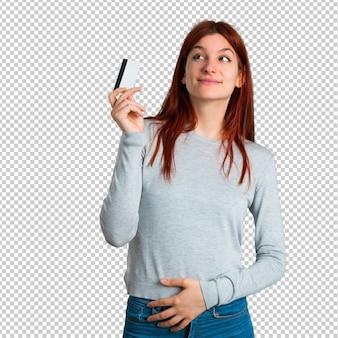Giovane ragazza rossa tenendo una carta di credito e pensando