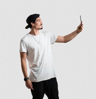 Giovane rapper uomo fiducioso e allegro, prendendo un selfie