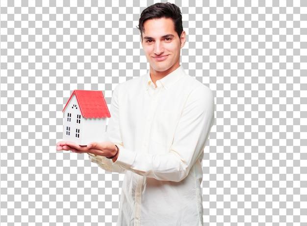 Giovane uomo abbronzato bello con un modello di casa