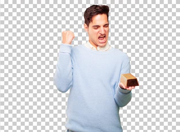 Giovane uomo abbronzato con un lingotto d'oro