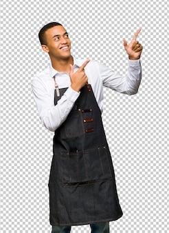 Giovane uomo afro american barbiere che punta con il dito indice e alzando lo sguardo