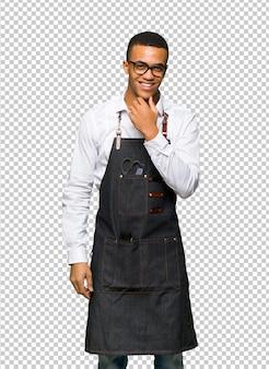 Giovane uomo afro american barbiere con gli occhiali e sorridente