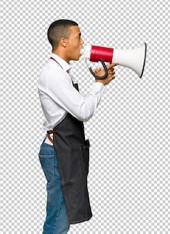 Giovane uomo afro american barbiere urlando attraverso un megafono per annunciare qualcosa in posizione laterale