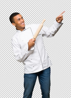 Giovane uomo afro american chef che punta con il dito indice e alzando lo sguardo