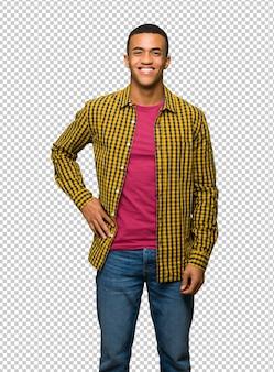 Giovane uomo afro american in posa con le braccia all'anca e sorridente