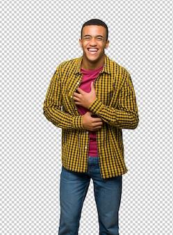 Giovane uomo afro american sorridente molto mentre mettendo le mani sul petto