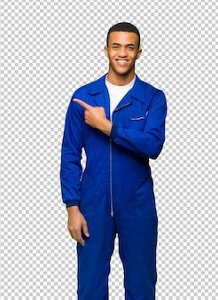 Giovane uomo afro american worker che punta al lato per presentare un prodotto