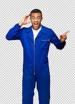 Giovane uomo afro american worker che punta il dito verso il lato e presentare un prodotto