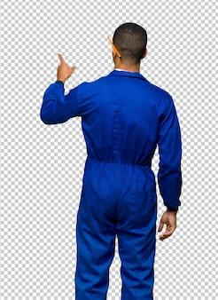 Giovane uomo afro american worker che punta indietro con il dito indice