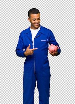 Giovane uomo afro american worker in possesso di un piggybank