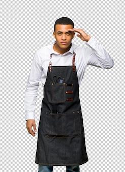 Giovane uomo afroamericano del barbiere che guarda lontano con la mano per guardare qualcosa