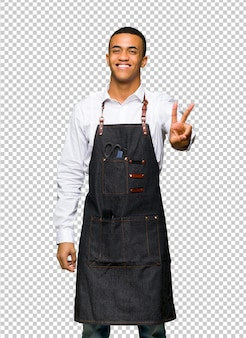 Giovane uomo afroamericano del barbiere che sorride e che mostra il segno di vittoria