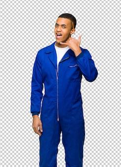 Giovane uomo afroamericano dell'operaio che fa gesto del telefono. chiamami segno