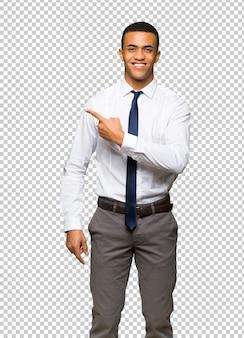 Giovane uomo d'affari afro americano che punta al lato per presentare un prodotto