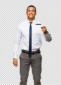 Giovane uomo d'affari afro americano che tiene una carta di credito