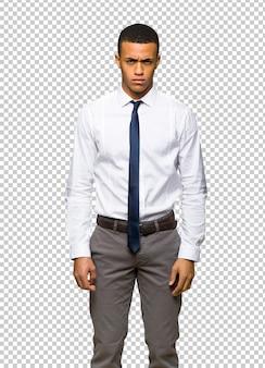 Giovane uomo d'affari afro americano con espressione triste e depresso