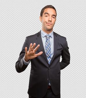 Giovane uomo d'affari serio che fa un gesto di calma della tenuta