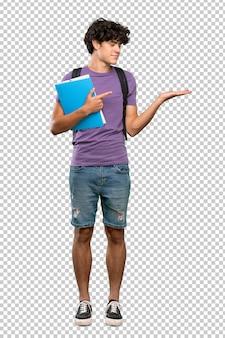 Giovane uomo dello studente che tiene copyspace immaginario sulla palma per inserire un annuncio