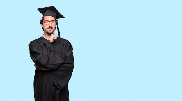 Giovane uomo laureato con uno sguardo confuso e pensieroso, guardando di traverso