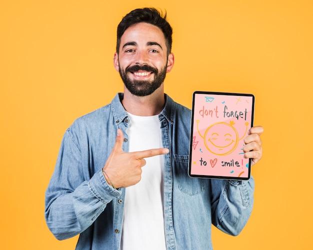 Glimlachende jonge mens die vinger richten op tabletspot omhoog