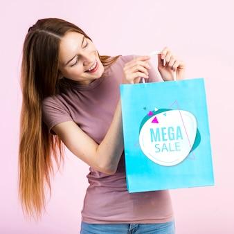 Glimlachende jonge vrouw die een papieren zak houdt