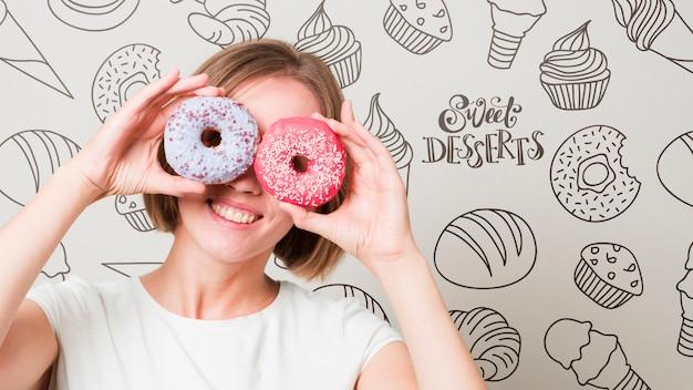 Glimlachende vrouw die door donuts kijkt
