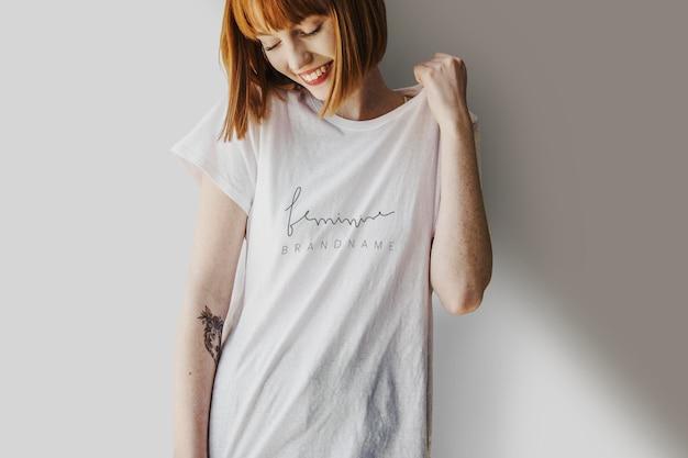 Glimlachende vrouw die een mockup met een zeefdrukwit t-shirt draagt