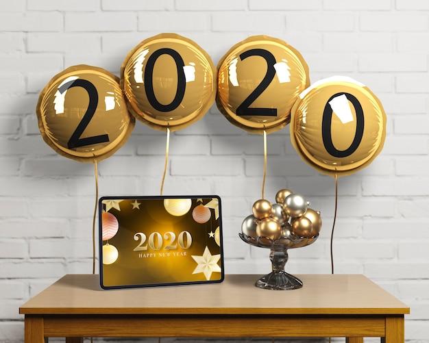 Globos con número de año nuevo y tableta