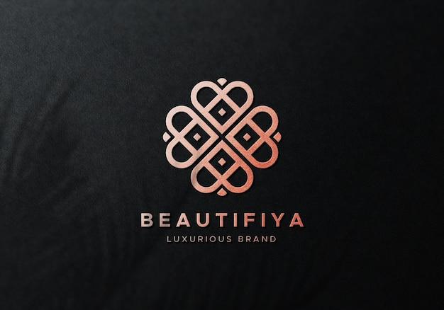 Goud verijdelde logo-mockup op zwarte achtergrond
