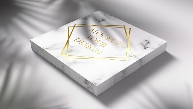 Gouden logo mockup op marmer met schaduwbladeren